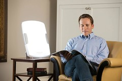 A man reading a magazine sitting on his couch witha SAD lamp on his side table (lightthereapydevice) Tags: a man reading magazine sitting his couch witha sad lamp side table