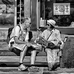 Discussing the Day's Headlines (Anne Worner) Tags: anneworner blackandwhite silverefex bw backpack bench candid conversation downtown hat man mono monochrome newspaper outside pants people shorts sitting storefront stores street streetphotography sunglasses tshirt talking woman canonpowershotg12 discussion discussing two sneakers soles barelegged bergen norway torgalmenningen candidstreetphotography naturallight daylight