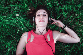Girl listens to music from her smartphone, with headphones.
