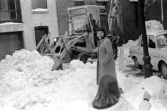 021469 26 (ndpa / s. lundeen, archivist) Tags: nick dewolf nickdewolf february blackwhite photographbynickdewolf bw 1969 1960s 35mm film monochrome blackandwhite boston massachusetts mass beaconhill snow snowremoval heavyequipment backhoe case casemotors woman child girl mother maggie nicole car vehicle automobile parkedcar building lamppost winter coat brunette bangs snowfall 10 renault r10