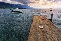 Hurry Home You Little Boat (Alfred Grupstra) Tags: nauticalvessel sea nature water woodmaterial lake outdoors pier landscape summer nopeople scenics jetty tranquilscene sky blue vacations harbor travel mountain macedonia ohrid
