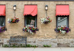 Red Awnings (Karen_Chappell) Tags: travel ontario window windows bench red brick building architecture flowers merrickville stone