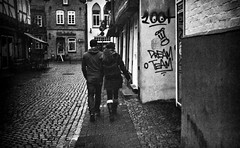 Dream Team (Mister G.C.) Tags: street urban photography blackandwhite bw ricoh ricohfz3000 ricohfz300 compactcamera pointshoot zoom zoomlens 38mm130mm streetphotography urbanphotography shot image photograph candid people graffiti juxtaposition kodakgold200 gritty couple man woman monochrome town city analog analogphotography analogue 35mm film schwarzweiss strassenfotografie mistergc germany niedersachsen lowersaxony deutschland europe