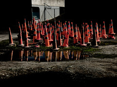 The Gathering at the Gates (Steve Taylor (Photography)) Tags: digitalart cone roadcone trafficcone fence chainlink contrast black stark orange green plastic gravel water puddle newzealand nz southisland canterbury christchurch reflection