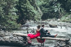 A beautiful young honeymoon couple posing on the river in the jungle of Bali island. (Artem Bali) Tags: couple married river young beautiful water bali jungle rainforest love woman happy man happiness people girl summer groom wife family wedding bride husband romance two travel together romantic dress marriage activity kiss beauty enjoy space smile creatingariver male relationship sunshine outdoor holding outdoors walk background holiday cheerful sea sunset spring