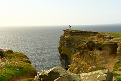 Hiker on Ledge (Eyes Open To Life) Tags: hiker cliffs coast coastline seascape nature landscape rocky rugged wildflowers