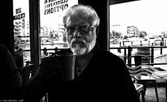 Coffee and puddle water. (Neil. Moralee) Tags: neilmoralee neilomoralee coffee cup mig man face portrait mature old beard white hair black monotome mono bw bandw blackandwhite drink drinking bristol menfolk power inspire passion docks neil moralee olympus omd em5 shadow harsh smooth taste monochrome life people gent chops glasses dark cheers addiction caffein c8h10n4o2