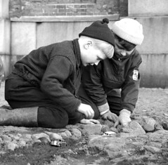 Playing with the miniature cars (theirhistory) Tags: children kids boy stones pavement hat cap jacket trousers rubberboots wellies