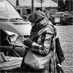 Book of Limericks (John Riper) Tags: johnriper street photography straatfotografie square vierkant bw black white zwartwit mono monochrome netherlands candid john riper sgravenhage denhaag thehague fuji fujifilm xt2 18135 woman book stall market limericks lady hat coat cold reading bag bike bicycle