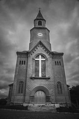A symetric facade of a Roman Catholic church from a small town in Minas Gerais, Brazil. A black and white image enphasize a big cross and the dramatic clouds in the sky. (pedroferr) Tags: stone dramatic minasgerais landscape window pray cloudy bw church exterior vintage southamerica trip architecture clouds religion holy desaturated contrast classic catholic travel door brazil arch sky cross jesus blackandwhite leopoldina god
