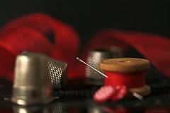 I spy with my little eye.... (eleni m) Tags: macro stilllife needle thimbles bobbin thread yarn buttons ribbon red wooden eye reflection dof bokeh metal black