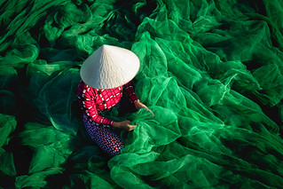 Vietnamese woman sitting repair the fishing net
