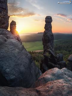 Rising sun behind rock needle