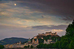 Nearly full moon over Salzburg (echumachenco) Tags: salzburg city building house architecture history art baroque medieval church cathedral kollegienkirche universitätskirche dom festung fortress castle hohensalzburg tree grass hill hillside green may spring sky cloud evening sunset moon fullmoon austria österreich nikond3100 spire