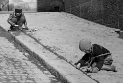 Digging up the pavement (theirhistory) Tags: children kids boy pavement road street hat coat jacket trousers wellies rubberboots