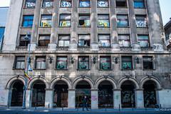 2018 - Romania - Bucharest - Rosenthal Bloc (Ted's photos - Returns 23 Jun) Tags: 2018 bucharest nikon nikond750 nikonfx romania tedmcgrath tedsphotos vignetting rosenthalbloc arches building oldbuilding streetscene street bollards flag graffiti nationalbankofromania