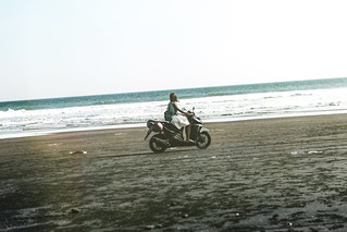 Young woman driving a scooter at the beach with black sand. Bali island.
