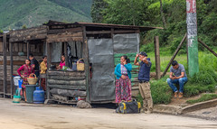 Waiting for the bus (Pejasar) Tags: people candid street waiting busstop guatemala rural travel shop store outdoor cellphone gathering color