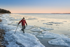 Solitary man hikes along icy shoreline of Ontario lake (blurMEDIA Stock) Tags: canada canadianshield earth georgianbay ontario ancient blue chemistry clean climate climatechange cold colortemperature cool crystal environment environmental explore fragile fragility freezing frigid frozen globalwarming ice icecube icicle icy journey kelvin lake lakeice landscape lifestyle light man melt mood nature north northern outdoor phasechange planet pure purity refreshing shoreline solitary solitude stewardship sunset thaw warm warming water whitebalance wilderness winter