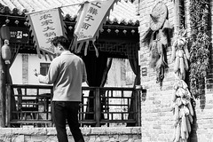 Meditation (Go-tea 郭天) Tags: qingdaoshi shandongsheng chine cn qingdao huangdao cangmashan ancient town village traditional tradition history historical historic house building construction past flag hat corn wall sun sunny shadow meditation man young alone lonely canon eos 100d 50mm prime street urban city outside outdoor people candid bw bnw black white blackwhite blackandwhite monochrome naturallight natural light asia asian china chinese shandong