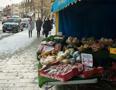 Fruit & Veg (M C Smith) Tags: pentax k3 walking pavement snow people women fruit veg sales shop cars parking parked display letters numbers symbols awning canopy blue yellow red green price buildings lamps packaging cardboard sealed packs sky grey slush pavingslabs