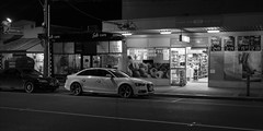 ferntree-gully-0029-ps-w (pw-pix) Tags: night dark shops supermarket cafe laundrette cars road street footpath lights pole lines parking quiet empty still bw blackandwhite monochrome alpinestreet ferntreegully easternsuburbs outereast melbourne victoria australia peterwilliams pwpix wwwpwpixstudio pwpixstudio