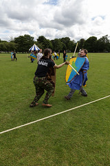 Historia Normannis Meadows June 2018-76 (Philip Gillespie) Tags: historia normannis central scotland sparring fighting shields swords axes spears park grass canon 5dsr men man women woman kids boys girls arms feet hands faces heads legs shins running outdoor tabards chain mail chainmail helmets hats glasses sun clouds sky teams solo dead act acting colour color blue green red yellow orange white black hair practice open tutorial defending attacking volunteer amateur kneeling fallen down jumping pretty athletic activity hit punch