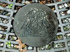 The Great Grating (Steve Taylor (Photography)) Tags: crest manhole grating digitalart design symbol metal gravel bird round leaf weeds shield emblem