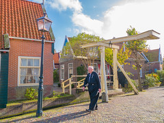 Old man in traditional Dutch costume (✦ Erdinc Ulas Photography ✦) Tags: old man traditional costume netherlands nederland dutch holland volendam panasonic culture building houses street bridge window stone bricks path road water moss tree light clouds sky blue roof