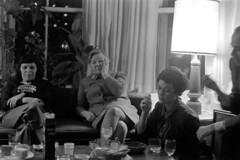 120769 04 (ndpa / s. lundeen, archivist) Tags: nick dewolf nickdewolf december photographbynickdewolf blackwhite bw 1969 1960s monochrome blackandwhite 35mm film boston massachusetts people socialvisit socializing woman women man sofa couch seated sitting snacks pretzels mistersaltypretzels drapes curtains window maggie necklace eatingpretzels drinks drinking alexdarbeloff