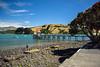 Dry Hills (Jocey K) Tags: bankspeninsula newzealand nikond750 akaroa akaroaharbour sea hills landscape boats yachts pier building stones seashore trees sky clouds people shadows pōhutukawa