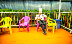 Colorful Thai chef! (Phg Voyager) Tags: thai thailand asia chef phgvoyager fun night color outdoor leica mp summilux bangkok restaurant people red yellow green white smartphone busy smile unreal colorful boy man pink chairs seated waiting bored 24mm empty funny pop kitch