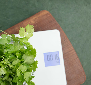 Weighing cilantro on digital scale.