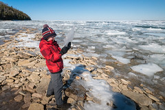 Boy examines sheets of ice at edge of frozen lake (blurMEDIA Stock) Tags: brucepeninsula canada earth georgianbay ontario child childhood climate climatechange cold conservation environment exploring fragile freezing frozen globalwarming ice icy lake lakeshore landscape learning melt melting outdoor phasechange planet preservation shoreline solitary solitude spring springthaw stewardship thaw warming water wilderness winter winterjacket