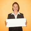 Businesswoman holding blank sign. (perfectionistreviews) Tags: indoors color square business professional businesswoman female women woman 3035years attractive caucasian brunette blanksign blank promote sign holding copyspace message advertise midadult youngadult signsandsymbols