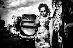 Dappled (Kieron Ellis) Tags: bus woman sunglasses dress bag walking lamppost sky clouds freckles street candid blackandwhite blackwhite monochrome