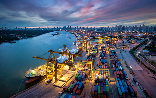 Aerial view of international port with Crane loading containers in import export business logistics with cityscape of Bangkok city Thailand at night