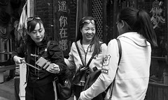 Tourists, Pingyao, China (chrisjohnbeckett) Tags: tourist selfie camera phone mobilephone cellphone technology stick people street candid portrait group blackandwhite monochrome bw chrisbeckett smile canonef24105mmf4lisusm pingyao china smartphone