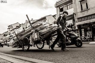 Woman Shouldering Wagon Alone