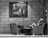The Conference Call (Anne Worner) Tags: anneworner blackandwhite em5 olympus silverefex bw candid chairs displaycase indoors inside library man mono painting phone sitting stone street streetphotography table talking wall floor art