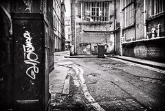 From days gone by. (Mister G.C.) Tags: street urban photography blackandwhite bw olympus xa2 olympusxa2 dzuiko zuikolens f35 35mm primelens fullframe lomographycolour400 compactcamera compact camera zone focus zonefocusing streetphotography urbanphotography shot image photograph backstreet alleyway alley textures old derelict decay decaying architecture lowpov lowpointofview graffiti leadinglines monochrome town city analog analogphotography analogue film filmcamera schwarzweiss strassenfotografie mistergc glasgow scotland europe
