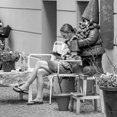 german idyll (every pixel counts) Tags: 2018 berlin mitte street eu dwarf people 11 bw everypixelcounts blackandwhite mobiledevice tablet cigarette woman berlinalive city day blackwhite bench reading cobblestones flowers pots