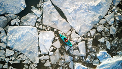 Aerial view of kayaker surrounded by ice of winter lake (blurMEDIA Stock) Tags: brucepeninsula canada earth georgianbay ontario pfd active aerial carpediem challenge climate climatechange determination environment environmental exercise fitness frozen fun globalwarming goodlife happy health healthy ice icy journey kayak kayaking lake lifejacket lifestyle living north northern outdoor perserverance planet refreshing rejuvenation relaxation retreat safety seasons skill solitary solitude sport warming winter wintersport