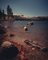 A view of a mountain by Donner Lake with some dramatic rocks on the foreground. (pedferr) Tags: horizon sunny sand color cinematic nature reflection moody lake 4x5 orange red blurry morning summer outdoors dramatic stone usa woods landscape water sky shapes unitedstatesofamerica vertical travel california texture summit mountain rocks bluesky longexposure snow adventure warm hill river brown hiking trails park colorful lifestyle detail