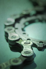 Spare parts (alideniese) Tags: macromondays transportation 7dwf anythinggoesmondays macro closeup chain link sprocket bicycleparts spareparts bicyclechain metal components bokeh light shadow texture colour green alideniese