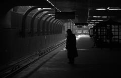 Inbound Man (VanveenJF) Tags: orangeline inbound man rain jacket sony boston bw street light dark silhouette train green forest hills