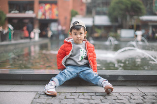 Portrait of a baby boy sitting in front of the fountain