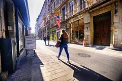 Walking through Grenoble, France (` Toshio ') Tags: toshio grenoble france french city woman walking road street europe european europeanunion shadow light fujixt2 xt2 shopping store