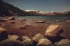 A view of a snow mountain by Donner Lake with some dramatic rocks on the foreground. (pedferr) Tags: horizon sunny cinematic nature water summit hill red blurry california summer outdoors horizontal dramatic stone usa landscape texture shapes lake clouds colorful closeup morning snow pattern rocks bluesky longexposure travel adventure warm unitedstatesofamerica river forest mountain 4x5 trails park purple woods sky detail