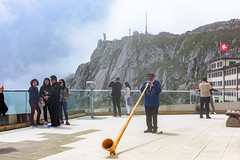On top of Mount Pilatus in Switzerland entertainment is provided by a gentleman playing the instrument called alpenhorn (ttchao) Tags: nikon d810 2470mm mountpilatus pilatus luzern lucerne switzerland alpenhorn